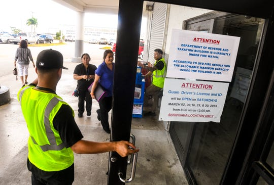 A notice, announcing a fire watch in progress, is posted at the entrance of the Department of Revenue and Taxation building, as DR Safety Consultant fire watch safety officers monitor the number of incoming and outgoing customers, in Barrigada on Thursday, March 21, 2019.
