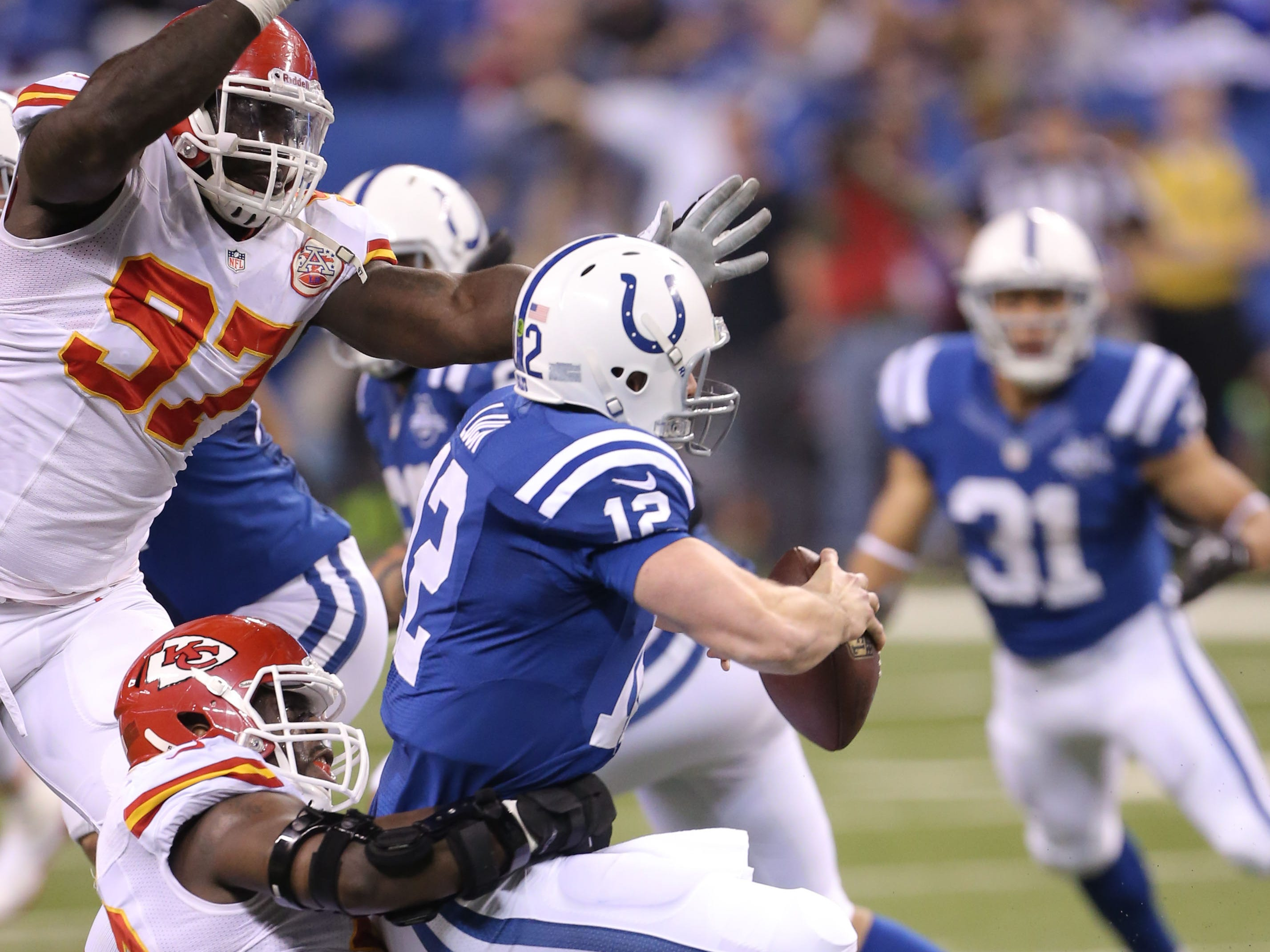 Indianapolis Colts Andrew Luck was  taken down by Kansas City Chiefs Justin Houston during the 2013 AFC Wildcard game  at Lucas Oil Stadium.