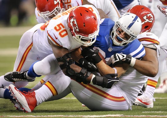 Indianapolis Colts running back Donald Brown was crushed between Kansas City Chiefs Justin Houston  (50) and Kansas City Chiefs Dontari Poe in the first half of their 2014 AFC Playoff game.