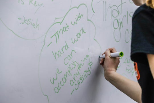 "Cassidy Felger, from the  S.M.A.C.K. Attack all girl robotics team, writes on the ""What has robotics taught me?"" wall, ""That with hard work, we can accomplish anything."" at Hamilton Heights Middle School in Arcadia Ind. on Tuesday, March 19, 2019."