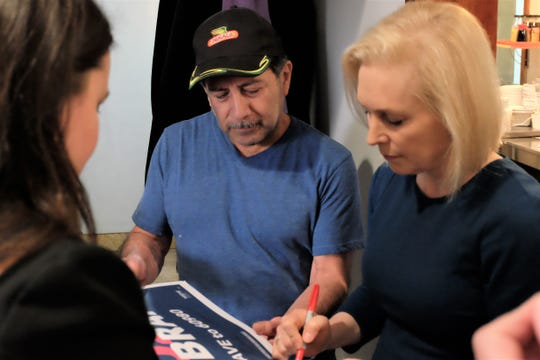 Sen. Kirsten Gillibrand, D-New York, signs a poster for Juan Galvez during her visit to RED Berry Diner in Muscatine Wednesday, March 20, 2019.