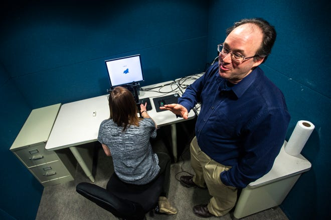 Bob McMurray, right, talks while University of Iowa clinical audiology student Kelsey Klein of Hoquiam, Washington, demonstrates an eye tracking test, Thursday, March 21, 2019, at Spence Laboratories of Psychology on the University of Iowa campus in Iowa City, Iowa. McMurray is a professor in the UI's Department of Psychological and Brain Sciences.