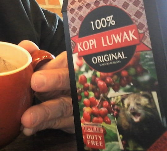 The face of an angry Asian palm civet graces this gift box of Kopi Luwak coffee, prompting a local writer's deeper pondering of international scatological beverages.