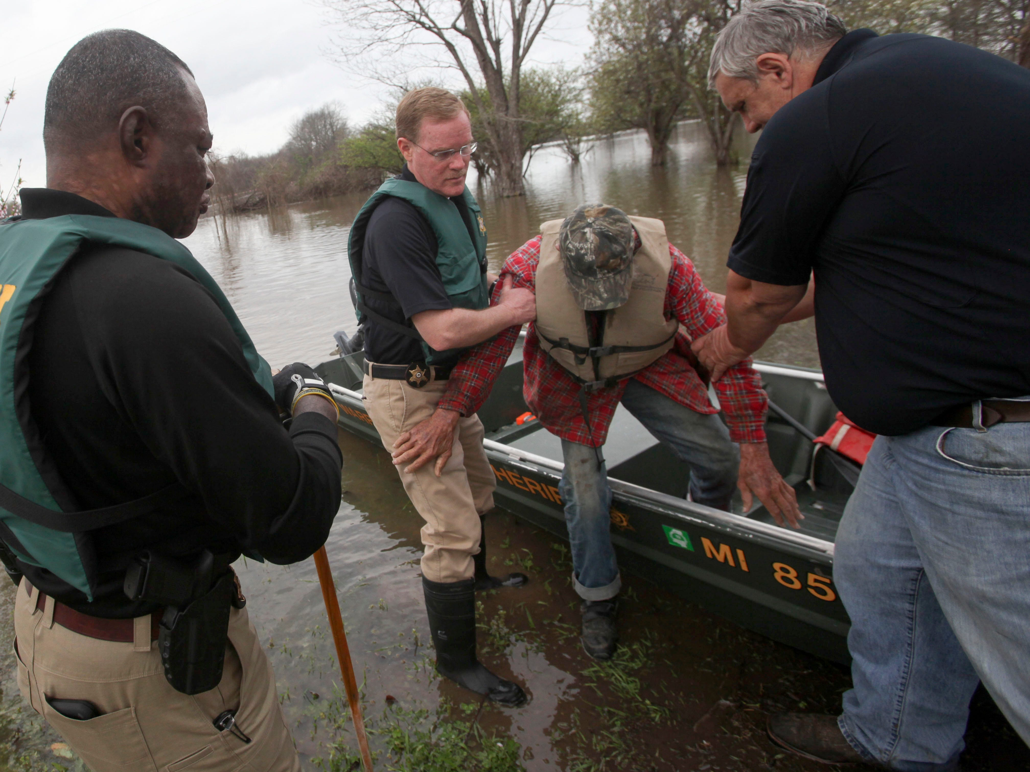 Warren County Sheriff Martin Pace and Reed Birdsong with Warren County Emergency Management help a man from a boat after assisting him with evacuating from his home that is inundated with floodwater off of Floweree Road in Redwood, Miss., Wednesday, March 13, 2019. Sheriff Pace said they were alerted by neighbors that there was a man alone and found his home surrounded by several feet of water with no vehicle or boat.