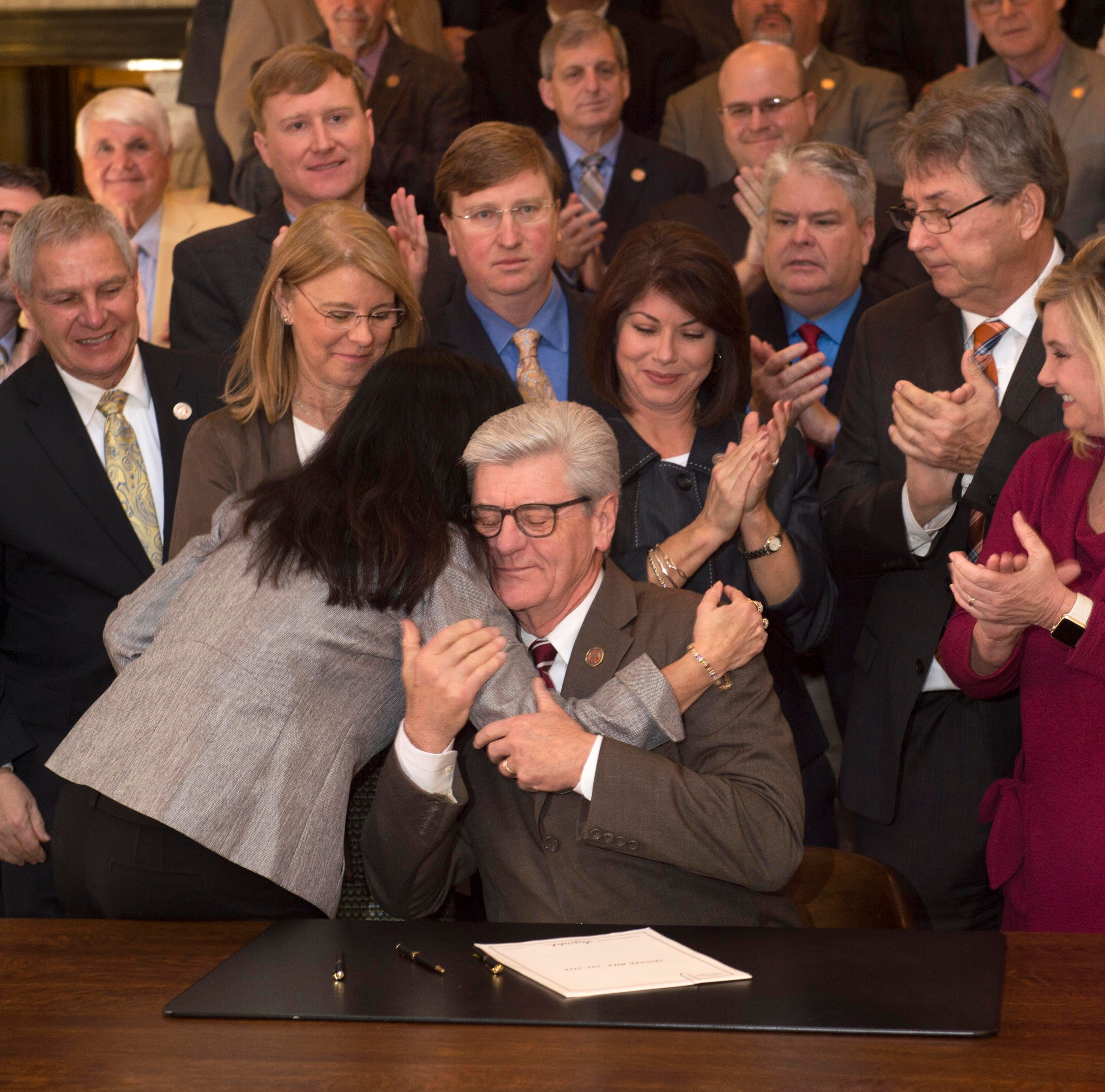 Surrounded by members of the Mississippi state legislature and other guests, Miss. Gov. Phil Bryant (seated) hugs Miss. Sen. Angela Hill-R, after Bryant signed into law what is commonly known as the Heartbeat Bill in Mississippi. The new legislation bans abortion procedures in Mississippi following the detection of a fetal heartbeat and is one of the most strict in the United States. Jackson, Miss. Thursday, March 21, 2019.