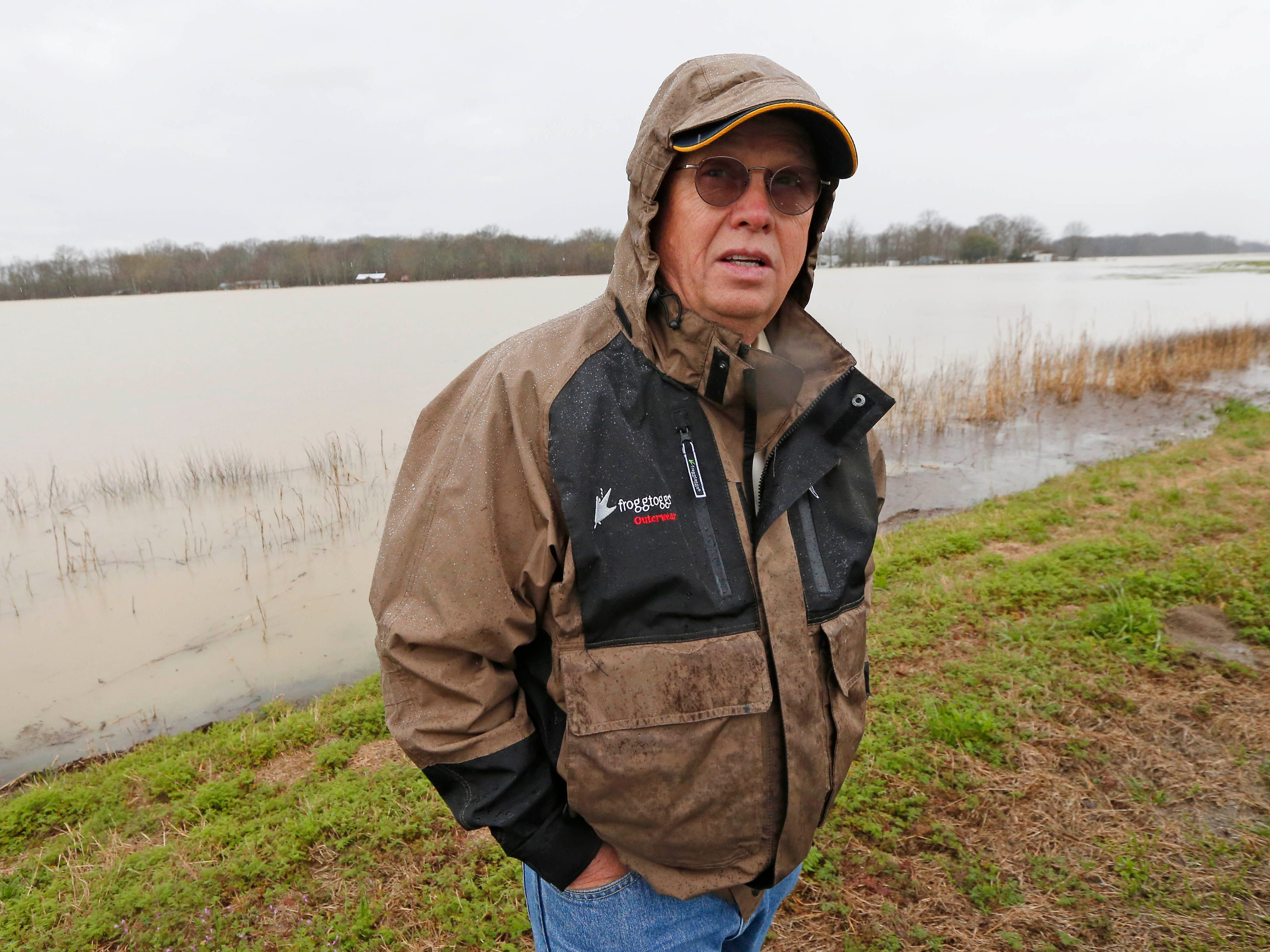 """In this Monday, March 11, 2019 photo, Sharkey County Supervisor Bill Newsom stands before a """"lake"""" of flood water that sits on top of farm lands usually covered with soybeans, near Rolling Fork, Miss. Newsom is an advocate of giant pumps that would move water out of the area, pushing it over the levee into a flooded Mississippi."""