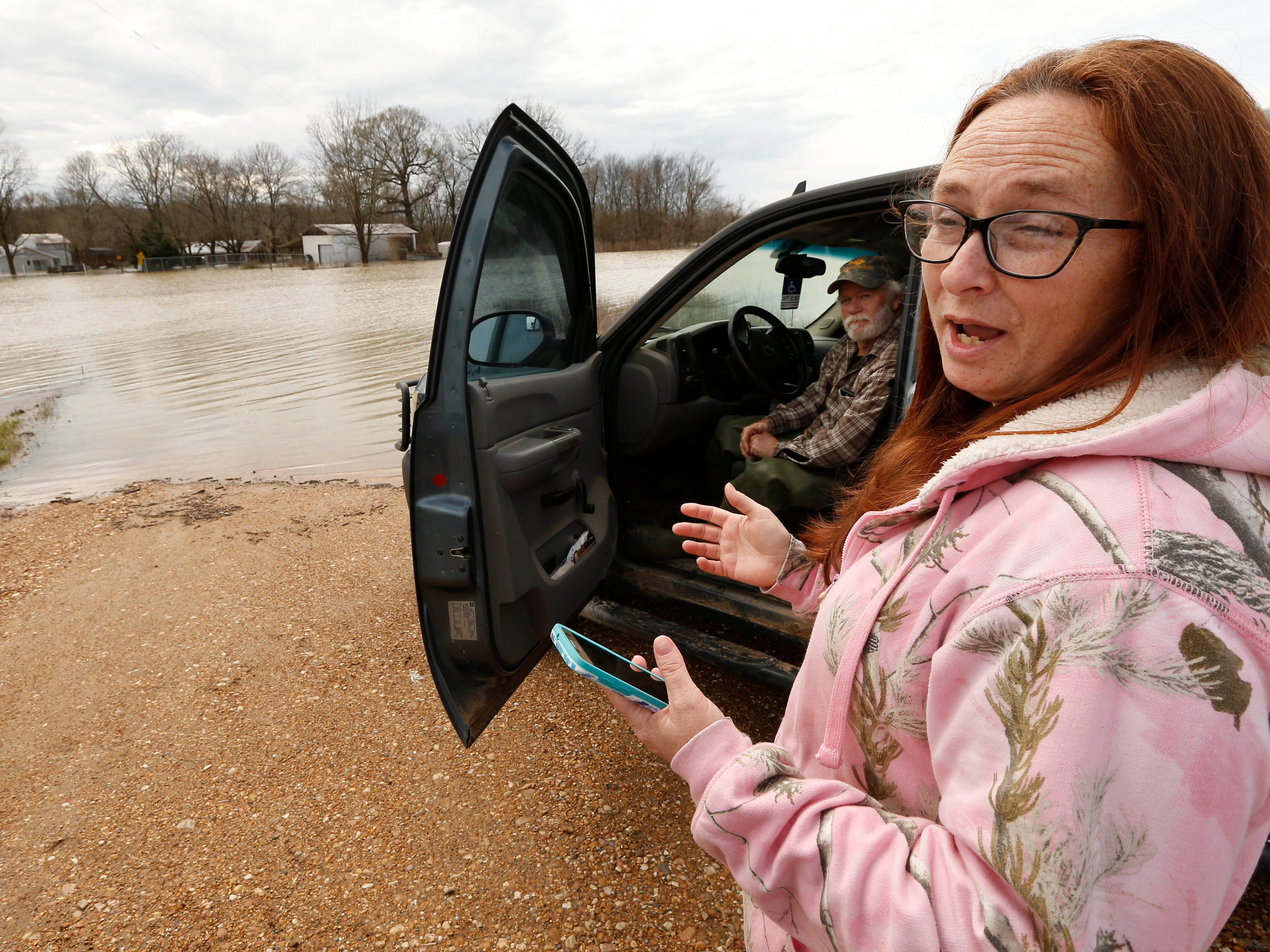 """In this Monday, March 11, 2019 photo, Peggy and her husband George Sellars sit by the """"lake"""" that was the driveway to their home, along Mississippi 16, east of Rolling Fork, Miss. The couple said the backwater flooding is the worse they have encountered and correctly concluded that water would overtop the retention levee that protected their house and three others."""