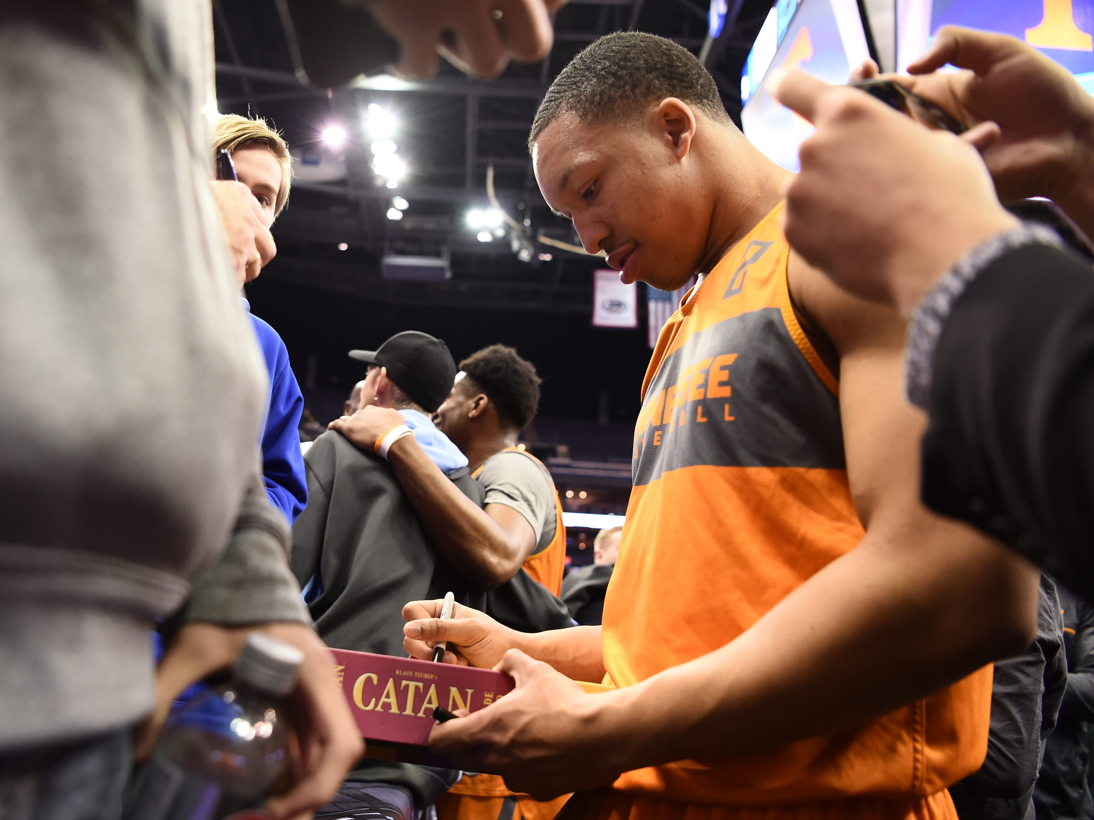 Tennessee forward Grant Williams (2) signs a fan's copy of the board game Catan after Tennessee's practice on Thursday, March 21, 2019, before their first round NCAA Tournament game against Colgate at Nationwide Arena in Columbus, Ohio.