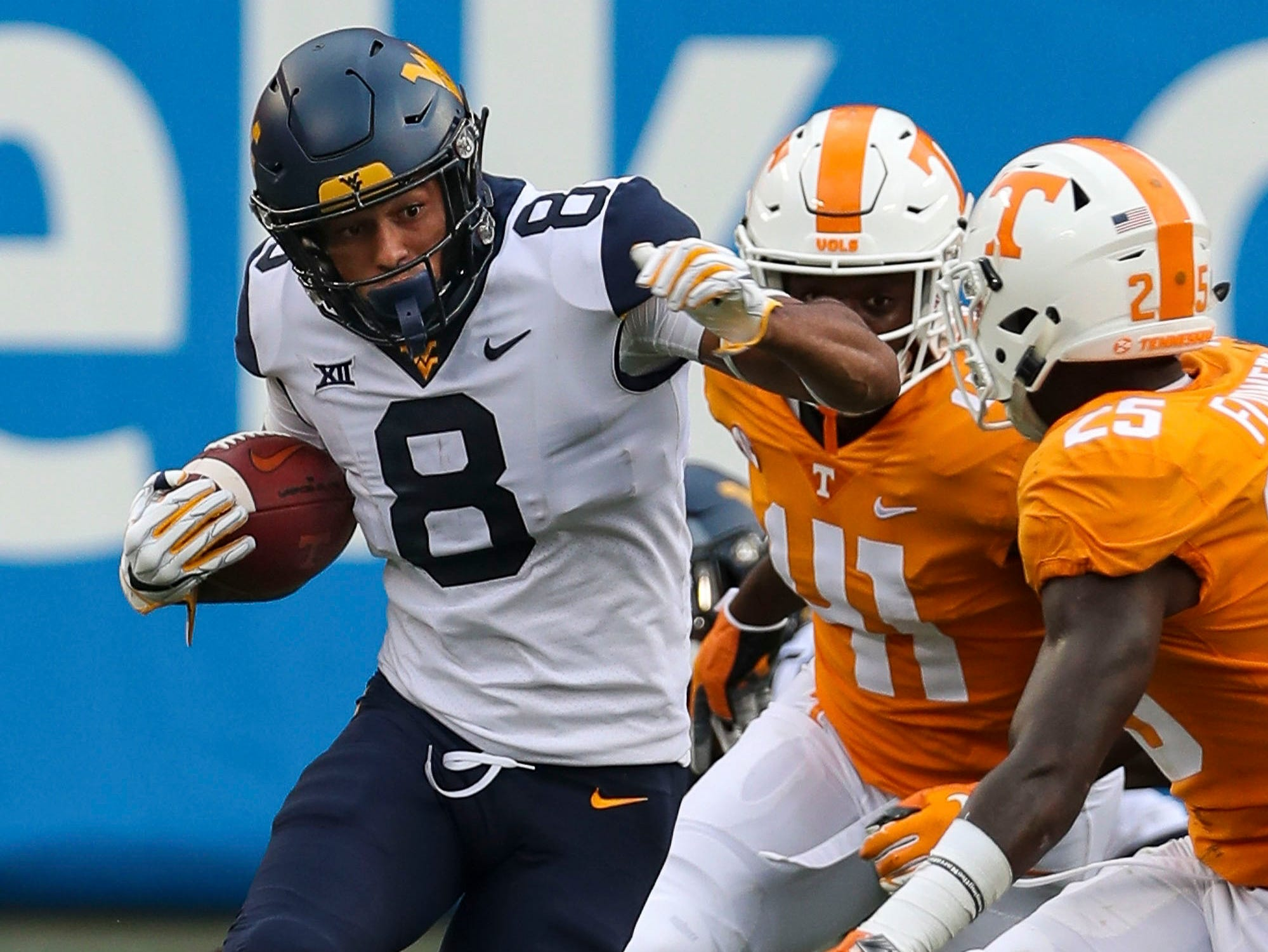 Sep 1, 2018; Charlotte, NC, USA; West Virginia Mountaineers wide receiver Marcus Simms (8) tries to elude Tennessee Volunteers defensive back Trevon Flowers (25) and defensive back Kenneth George Jr. (41) during the second half at Bank of America Stadium.