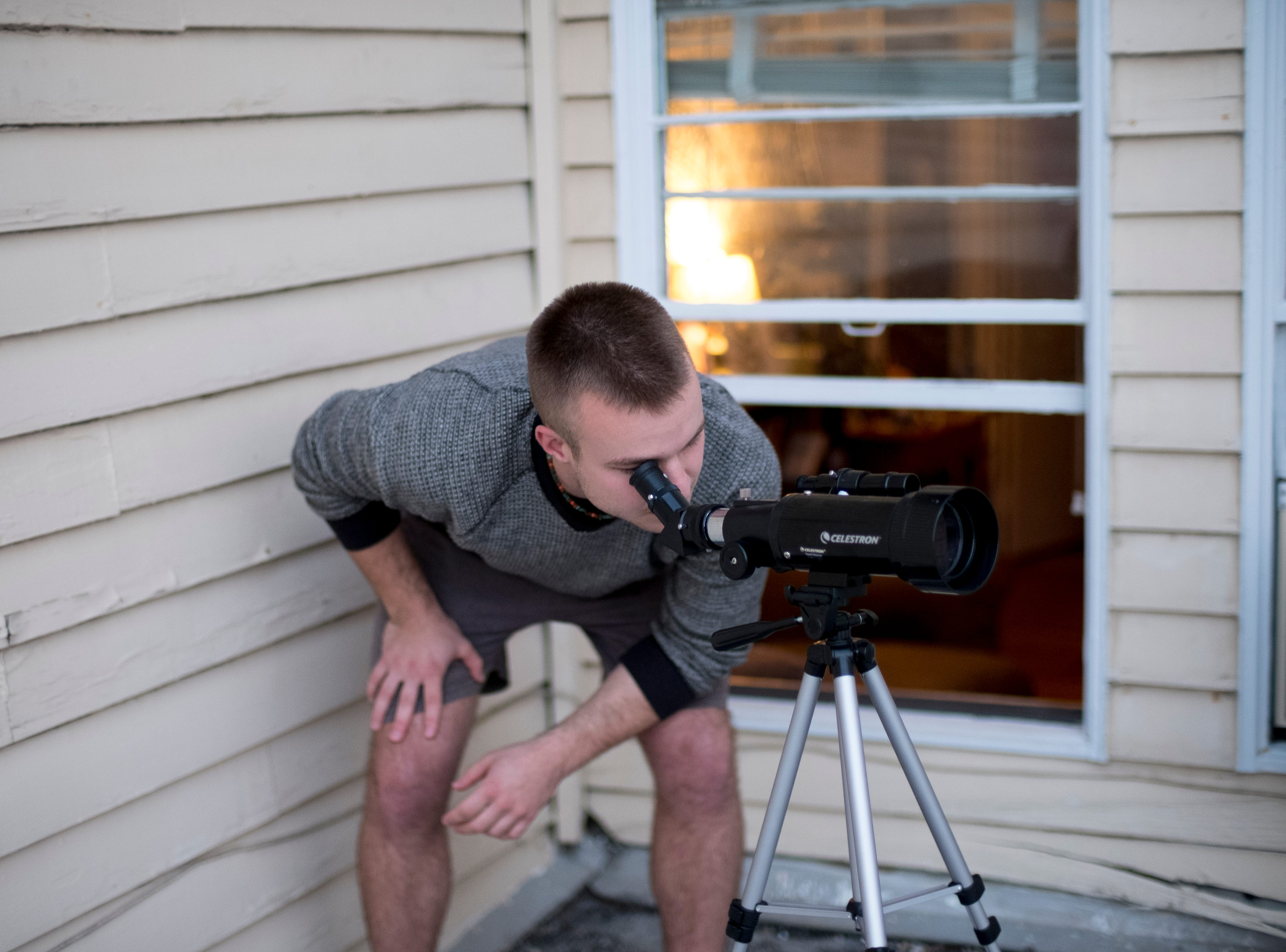 Cole Hoffman watches the 'super worm equinox supermoon' rise with a Celestron telescope he got for Christmas from the roof of his home on Laurel Ave in Knoxville, Tennessee on Wednesday, March 20, 2019. The last supermoon of 2019 gets its name since it coincides with the spring equinox and folklore where it says as the frosty ground melts, earthworms begin emerging.