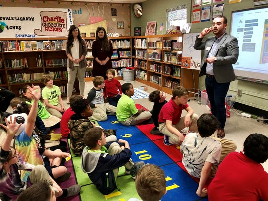 Jorey Krupa (right), community business development manager for Barnes & Noble in Lafayette, speaks to Woodvale Elementary students Tuesday at a Robotics Club meeting. Each student received a $5 gift card to Barnes & Noble after presenting their project.