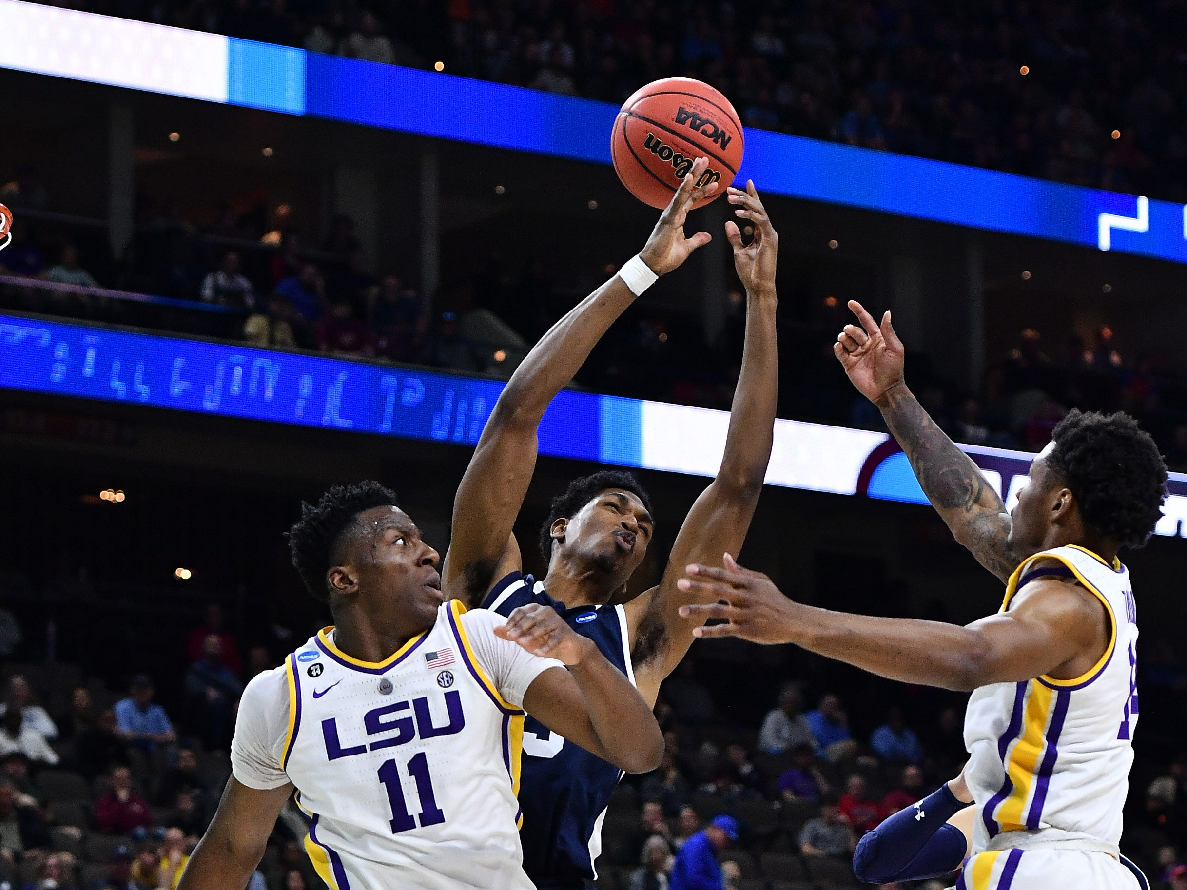 Mar 21, 2019; Jacksonville, FL, USA; Yale Bulldogs forward Jordan Bruner (middle) battles LSU Tigers forward Kavell Bigby-Williams (11) and guard Marlon Taylor (right) during the first half in the first round of the 2019 NCAA Tournament at Jacksonville Veterans Memorial Arena. Mandatory Credit: John David Mercer-USA TODAY Sports