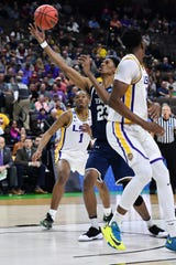 Mar 21, 2019; Jacksonville, FL, USA; Yale Bulldogs forward Jordan Bruner (23) shoots against LSU Tigers guard Javonte Smart (1) and forward Kavell Bigby-Williams (right) during the first half in the first round of the 2019 NCAA Tournament at Jacksonville Veterans Memorial Arena. Mandatory Credit: John David Mercer-USA TODAY Sports