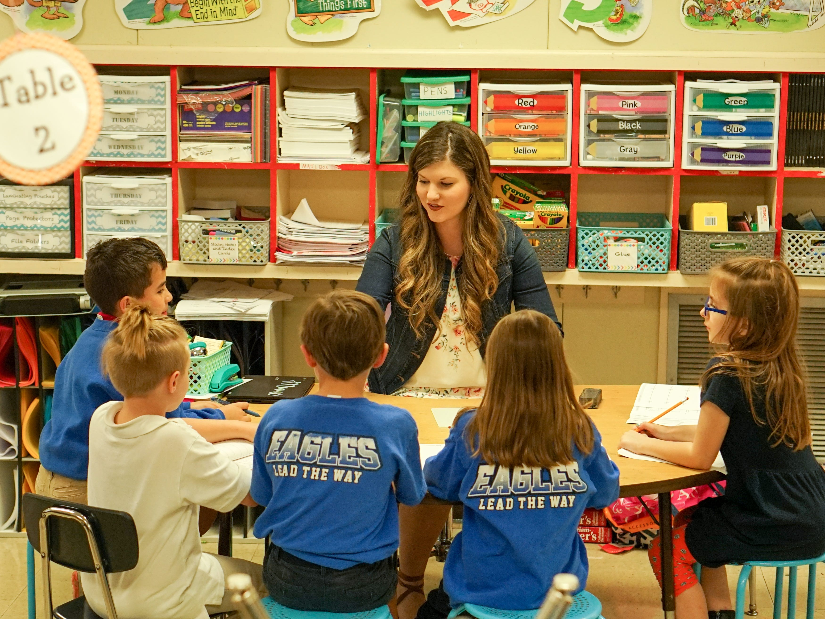 Twin sisters Taylor Wallace and Morgan Mercado share the same love for teaching at Woodvale Elementary. Here, Wallace works with her third-graders.