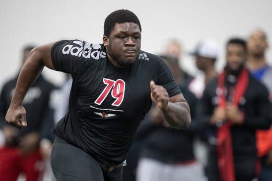 Offensive lineman Kenny Thomas runs agility drills during the pro day tryouts at the Trager Stadium indoor facility at U of L on Thursday. March 21, 2019