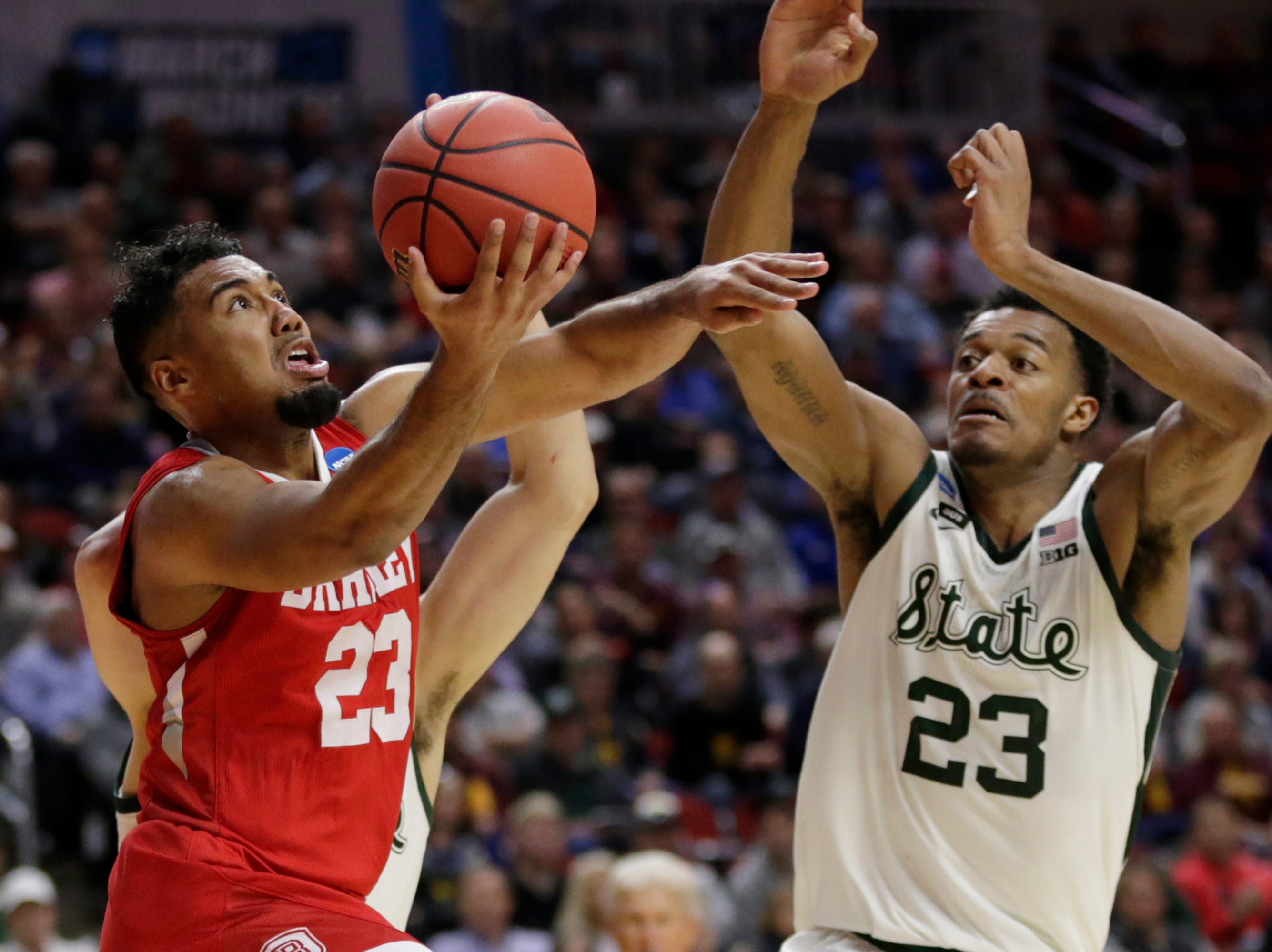 Bradley's Dwayne Lautier-Ogunleye (23) goes for a basket against Michigan State's Xavier Tillman, right, and Conner George, rear, during the first half of a first round men's college basketball game in the NCAA Tournament in Des Moines, Iowa, Thursday, March 21, 2019.