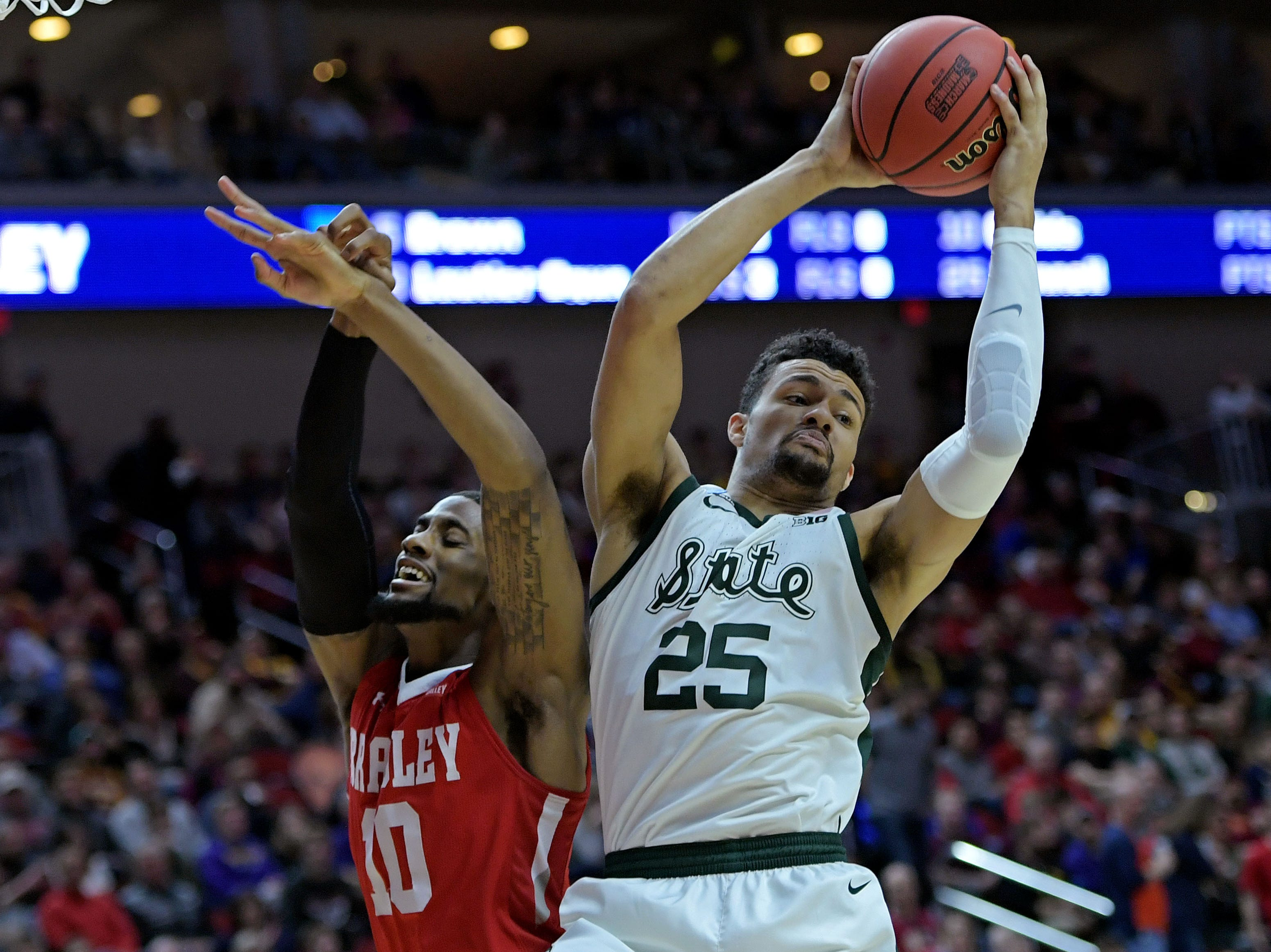 Michigan State Spartans forward Kenny Goins (25) and Bradley Braves forward Elijah Childs (10) go for a rebound during the first half in the first round of the 2019 NCAA Tournament at Wells Fargo Arena.