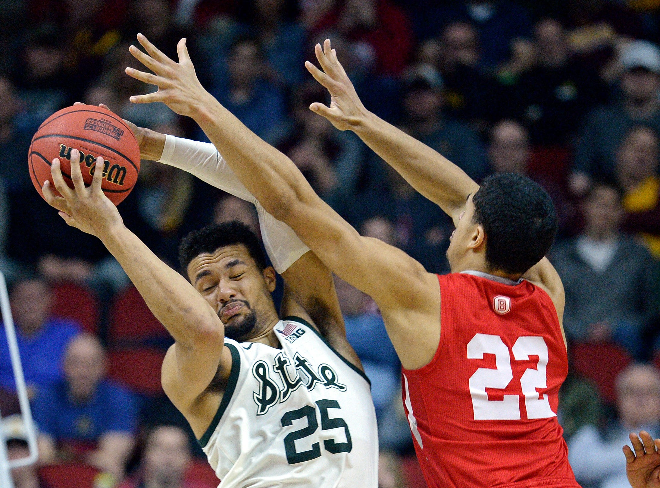 Michigan State Spartans forward Kenny Goins (25) and Bradley Braves guard Ja'Shon Henry (22) go for a rebound during the second half in the first round of the 2019 NCAA Tournament at Wells Fargo Arena.