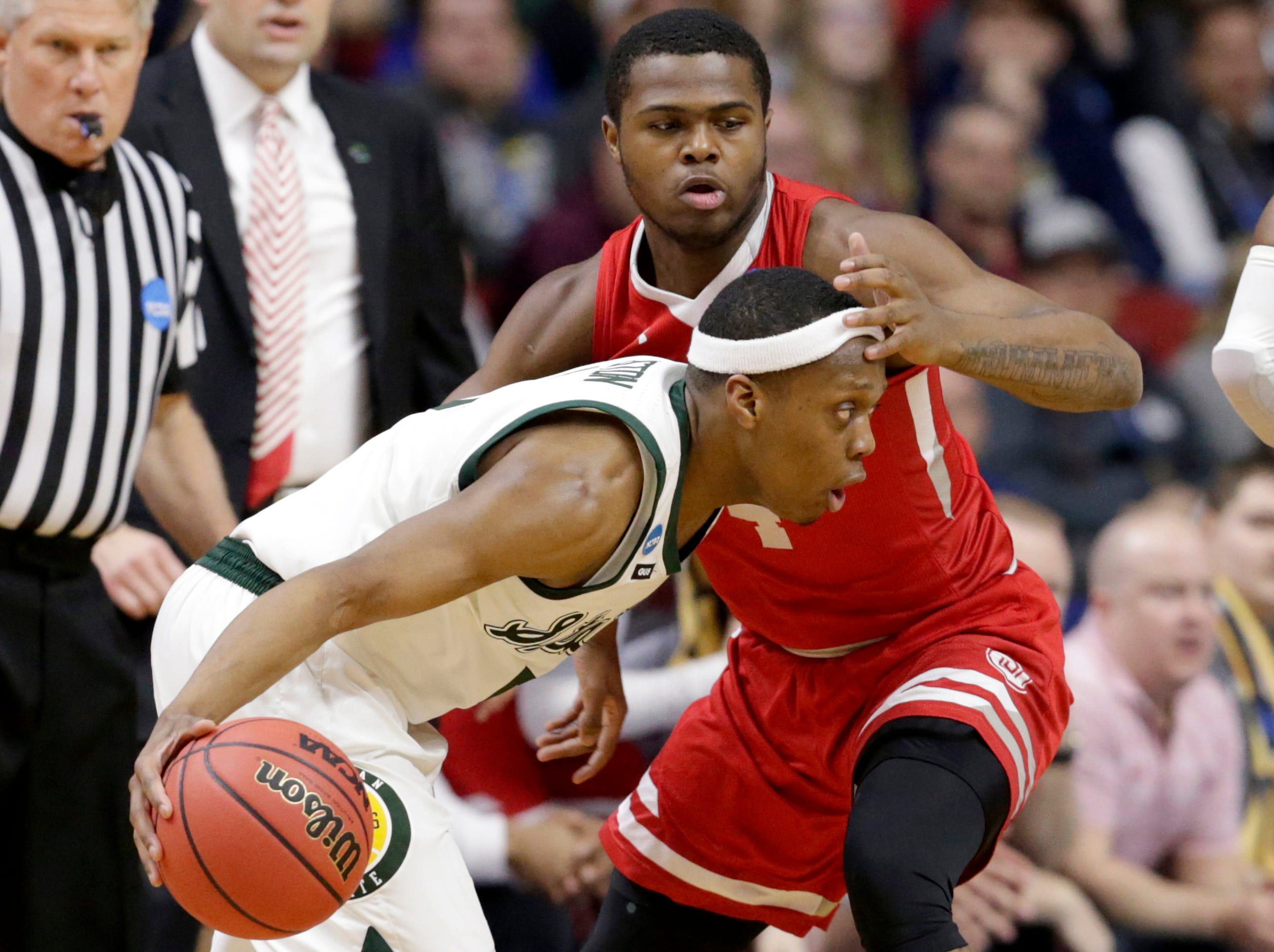 Michigan State's Cassius Winston, front, drives around Bradley's Armon Brummett, rear, during the first half of a first round men's college basketball game in the NCAA Tournament in Des Moines, Iowa, Thursday, March 21, 2019.