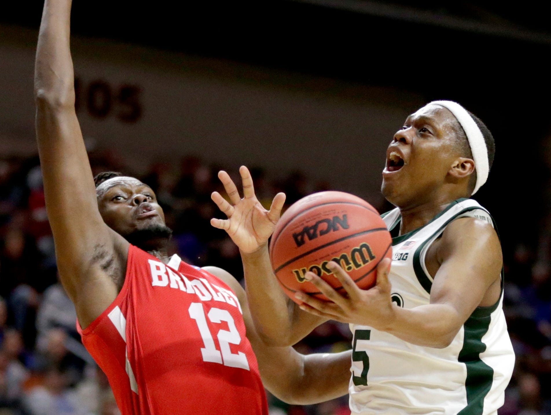 Michigan State's Cassius Winston (5) goes to the basket against Bradley's Koch Bar (12) during the second half of a first round men's college basketball game in the NCAA Tournament in Des Moines, Iowa, Thursday, March 21, 2019.