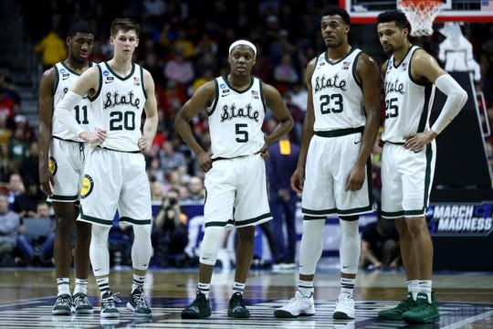 Aaron Henry #11, Matt McQuaid #20, Cassius Winston #5, Xavier Tillman #23, and Kenny Goins #25 of the Michigan State Spartans stand on the court during their game in the First Round of the NCAA Basketball Tournament against the Bradley Braves at Wells Fargo Arena on March 21, 2019 in Des Moines, Iowa.