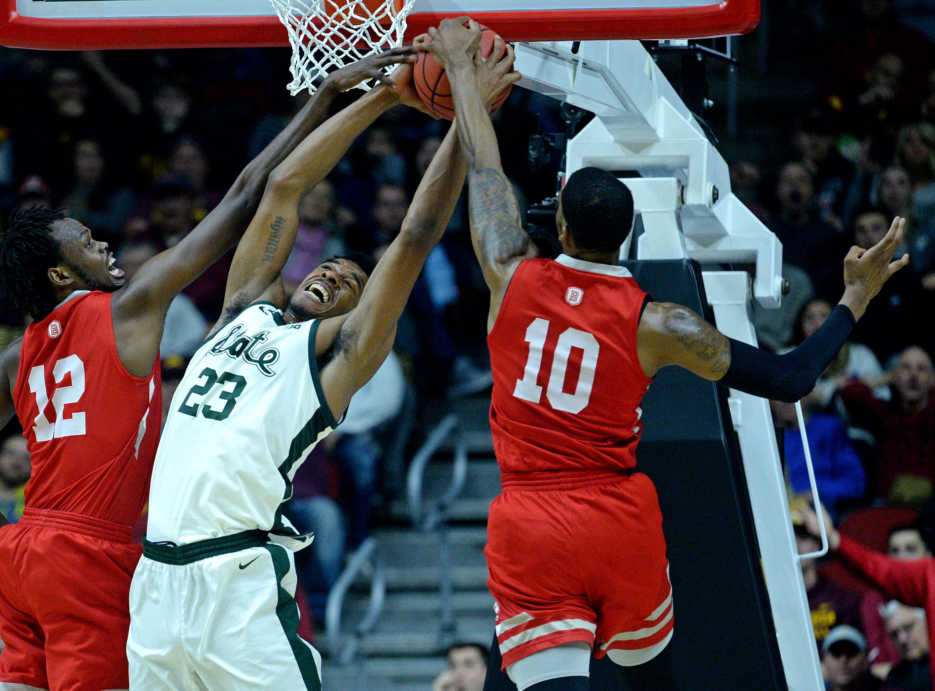 Bradley Braves center Koch Bar (12) and forward Elijah Childs (10) go for a rebound against Michigan State Spartans forward Xavier Tillman (23) during the first half in the first round of the 2019 NCAA Tournament at Wells Fargo Arena.