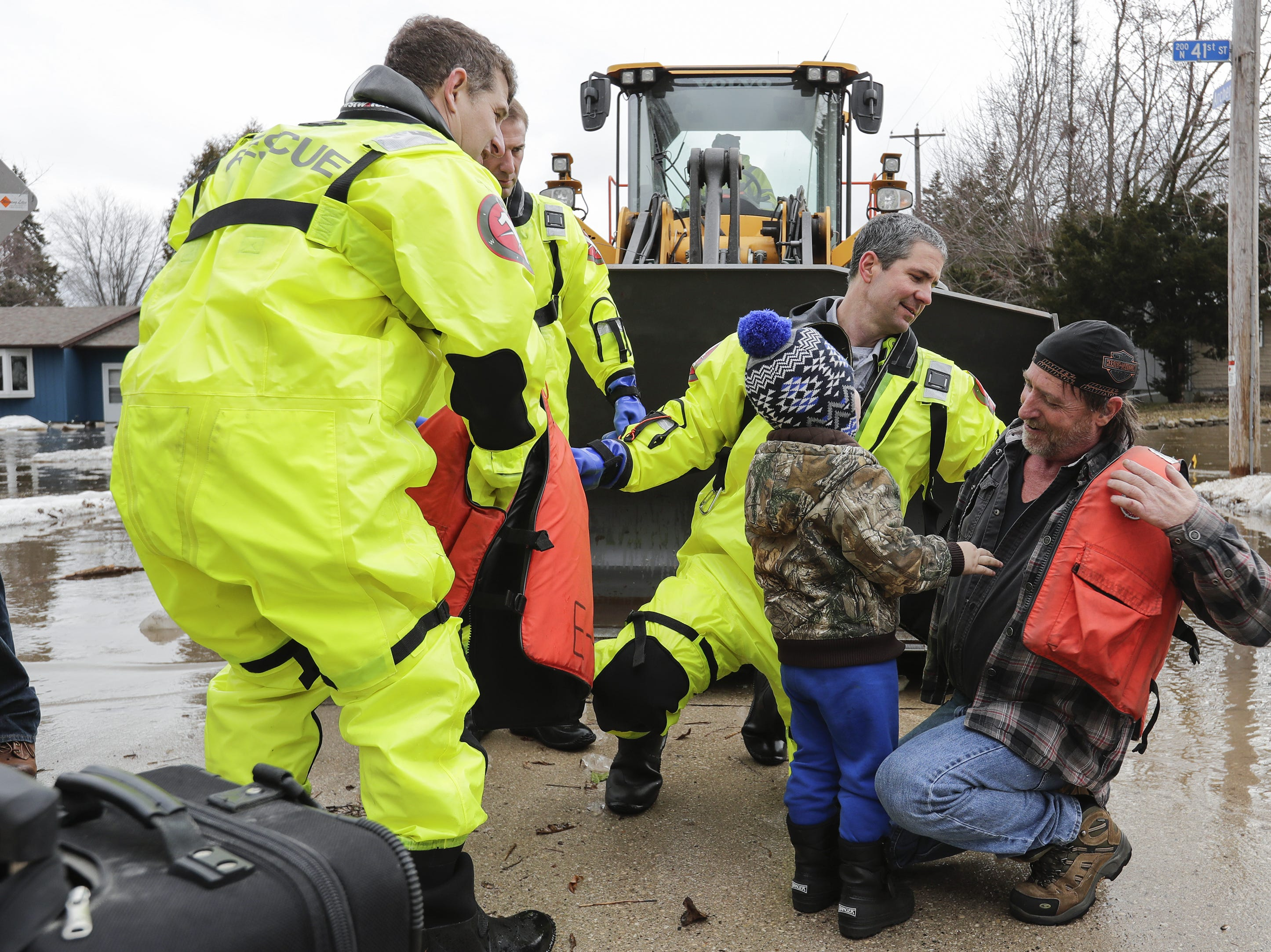 Firefighter Garrett Grissom helps Keith Pfeifer with his life vest after evacuating from 41st and Archer March 21 in Manitowoc.