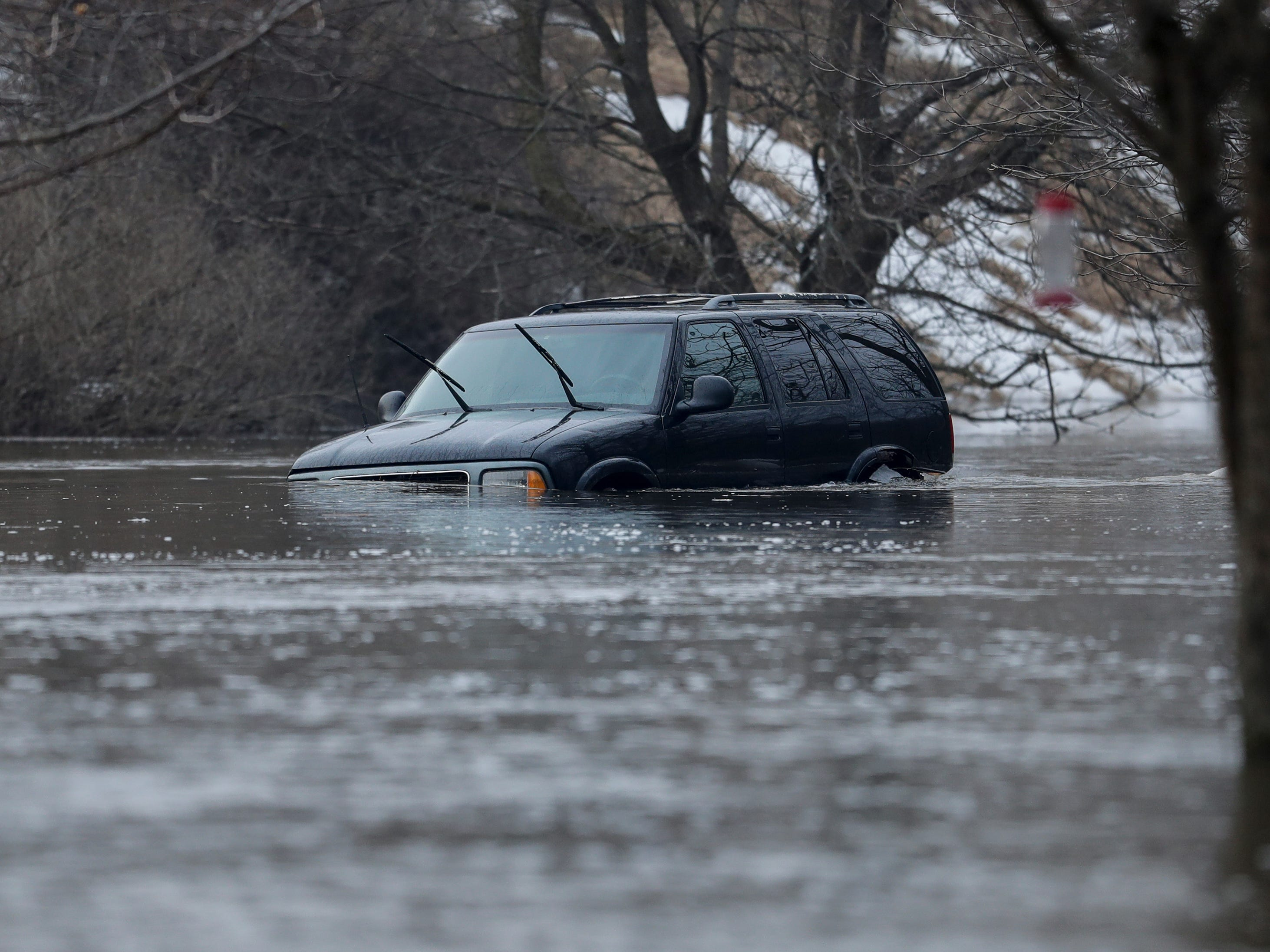A car parked on a property on Mill Road is under water after an ice jam on the Manitowoc River causes severe flooding Wednesday, March 20, 2019, in Manitowoc, Wis. Joshua Clark/USA TODAY NETWORK-Wisconsin