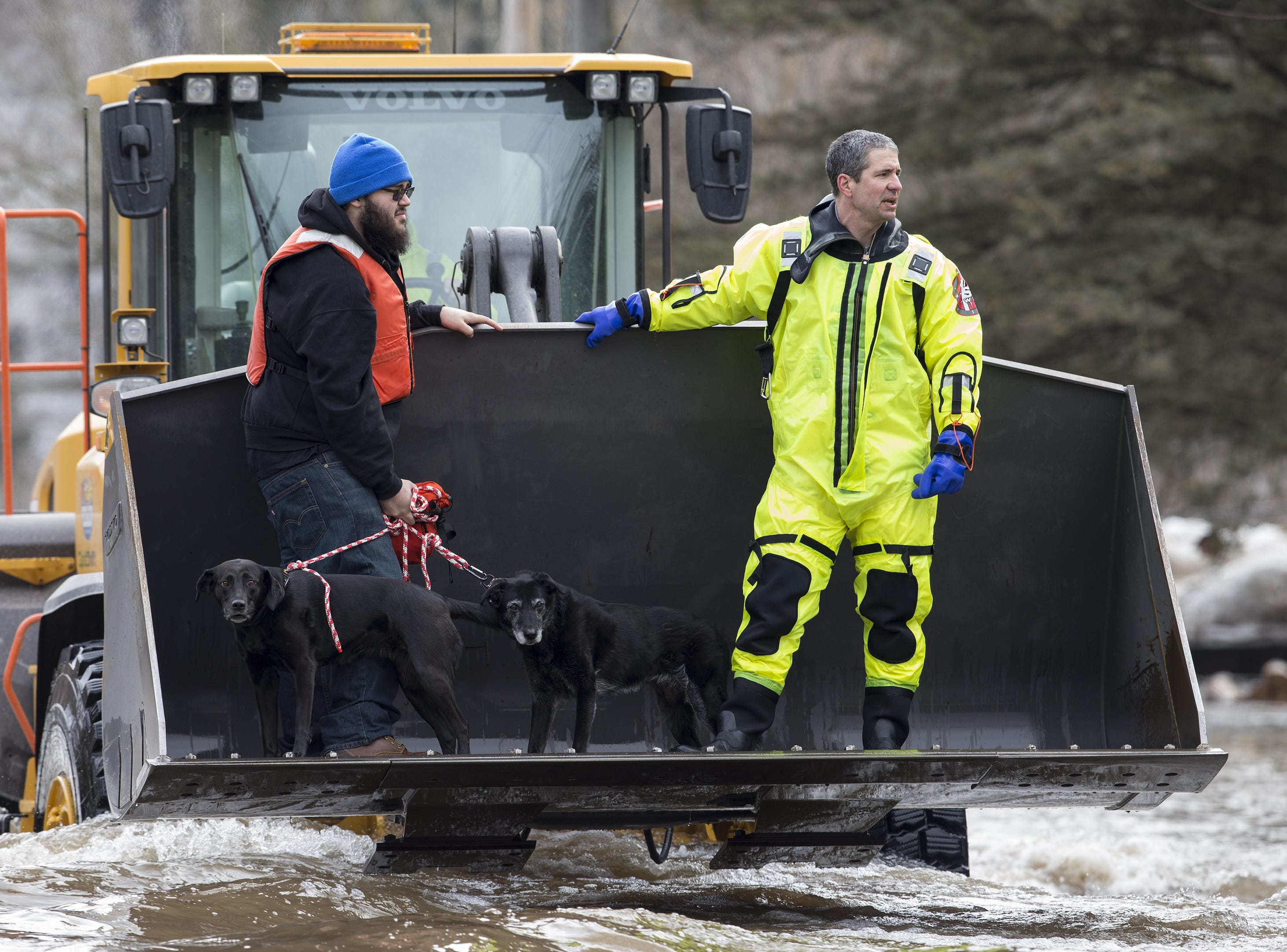 Ethan Perez and his dogs are evacuated from his residence at 41st and Archer by firefighter Garrett Grissom Thursday, March 21, 2019, in Manitowoc.