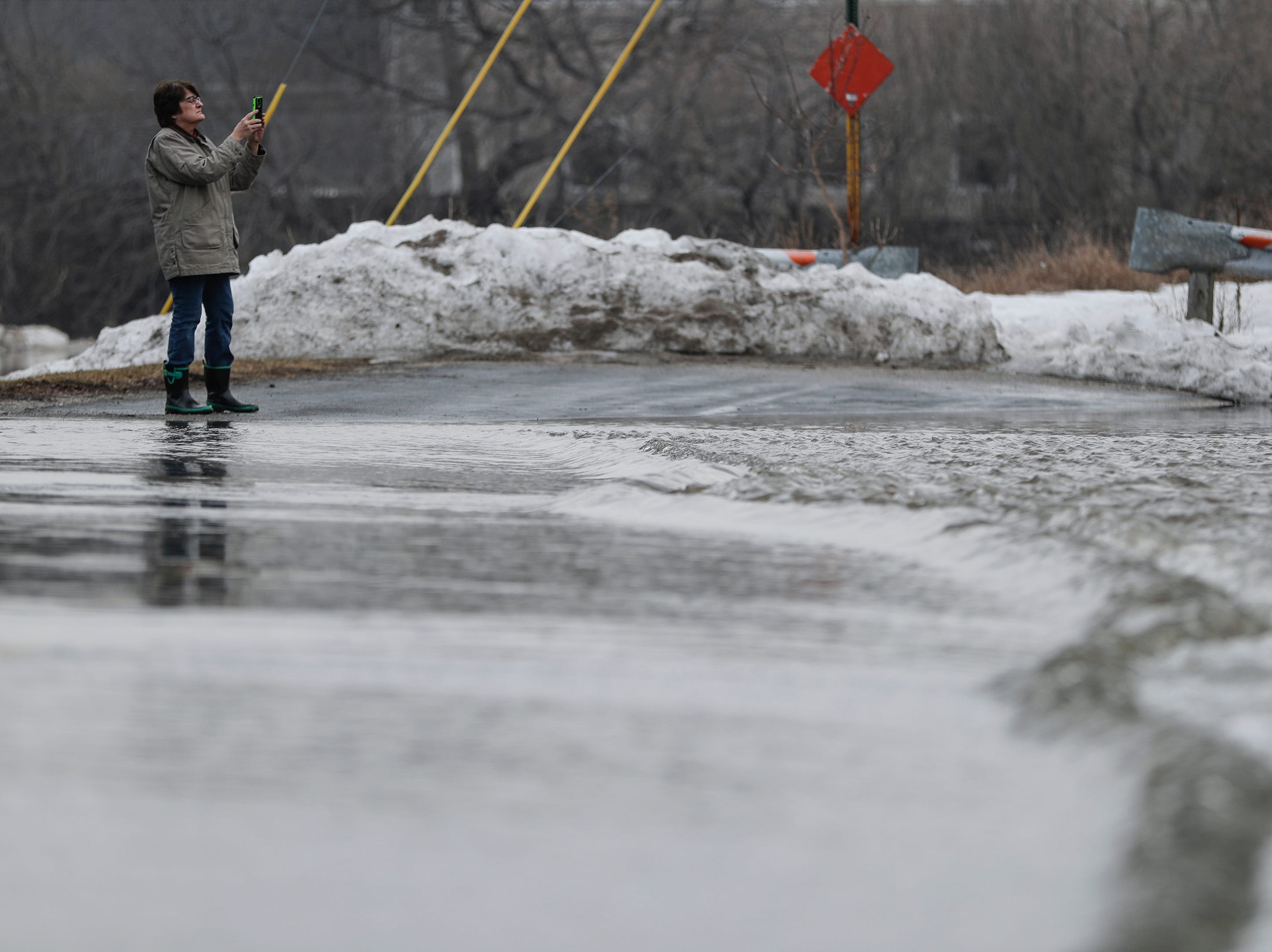 A woman takes a picture of the rising water after an ice jam on the Manitowoc River causes flooding on Mill Road Wednesday, March 20, 2019, in Manitowoc, Wis. Joshua Clark/USA TODAY NETWORK-Wisconsin