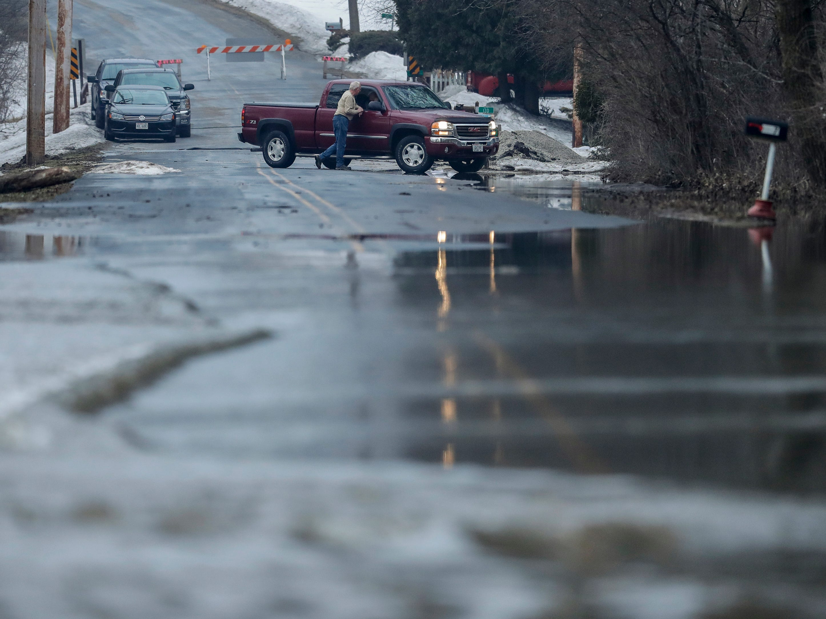 Water rises on Mill Road after an ice jam forms on the Manitowoc River Wednesday, March 20, 2019, in Manitowoc, Wis. Joshua Clark/USA TODAY NETWORK-Wisconsin