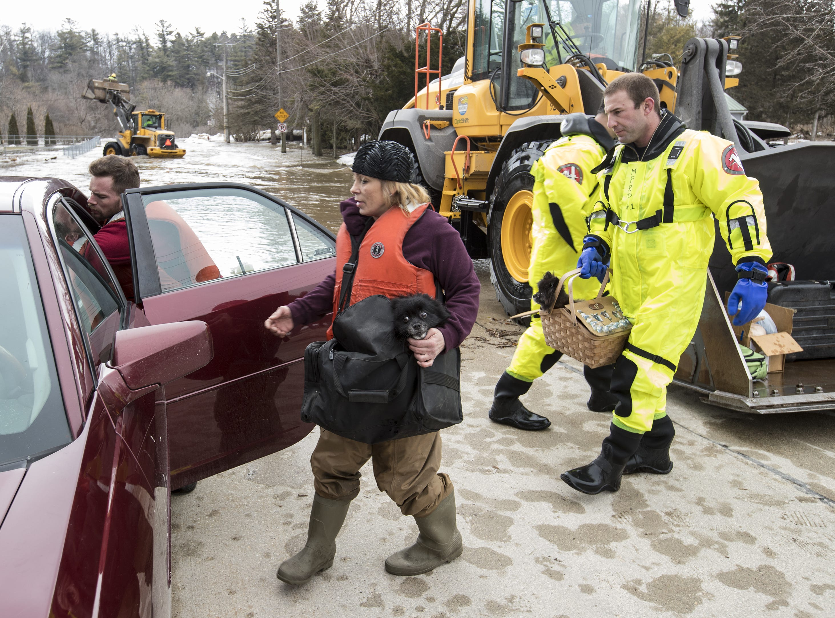 Annette Soukup loads her dog and belongings into her car with help from firefighter Kevin Fabian after being evacuated from her residence at 41st and Archer due to flooding on the Manitowoc River March 21 in Manitowoc.