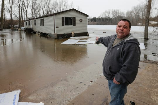 Joe Reindl points to how high the water level was on his property after flooding earlier this week Wednesday, March 20, 2019, in Two Rivers, Wis. Joshua Clark/USA TODAY NETWORK-Wisconsin