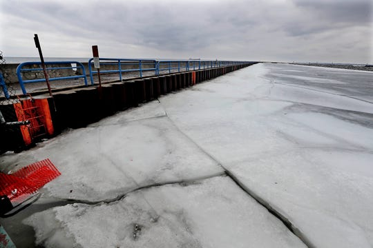 Heavy winter snows and ice finally begins to melt in the Milwaukee Harbor by a boat launching facility along Lake Michigan.