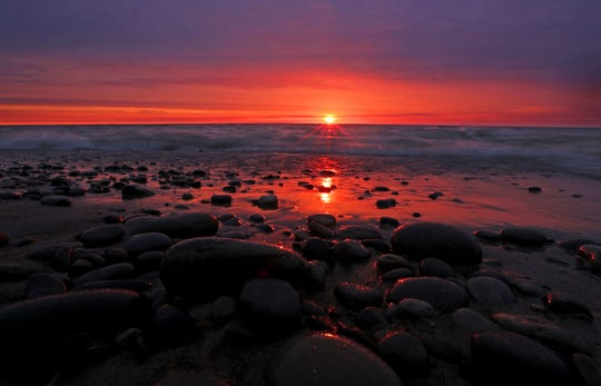 The sun rises over Lake Michigan along the shore of Doctors Park in Fox Point.