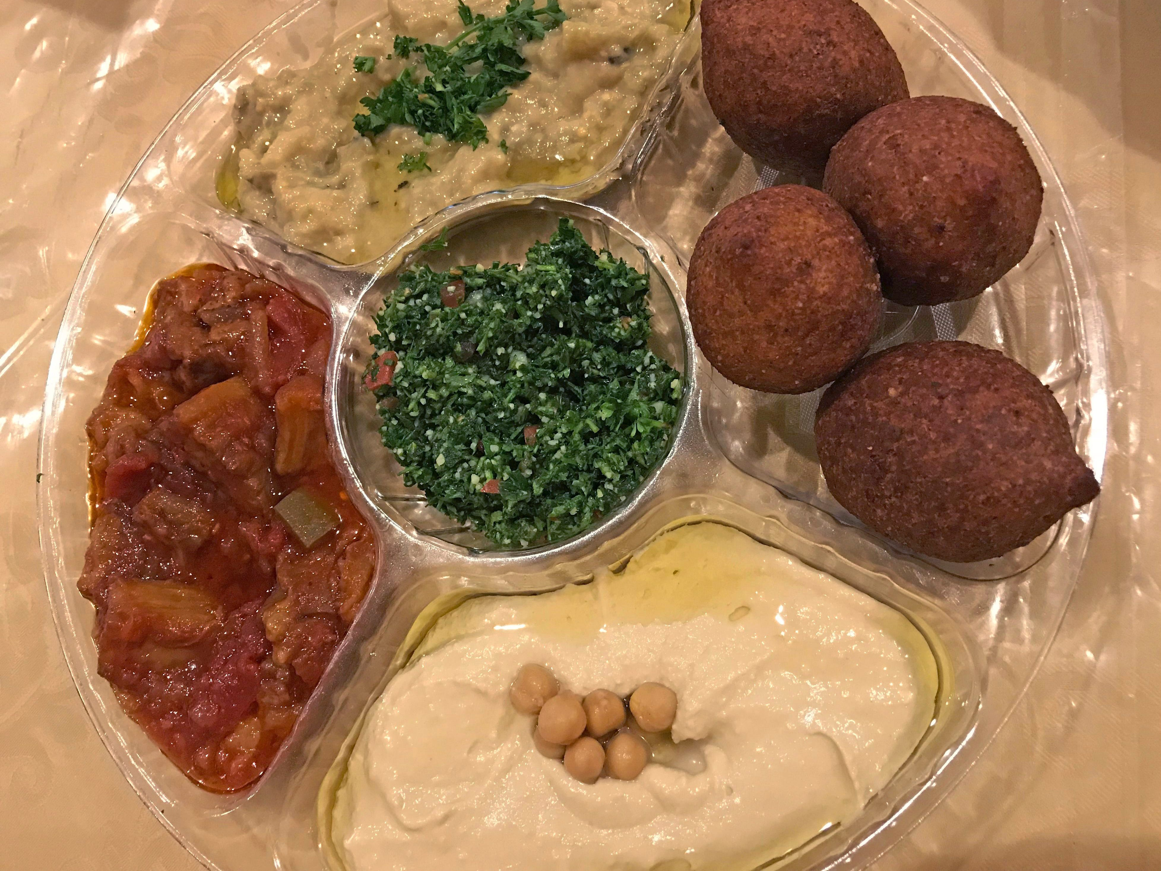 The mixed appetizer plate at Damascus Gate has (clockwise from top) baba ghanouj, meat-filled kibbeh, hummus, mousaaka and (in the center) tabbouleh.