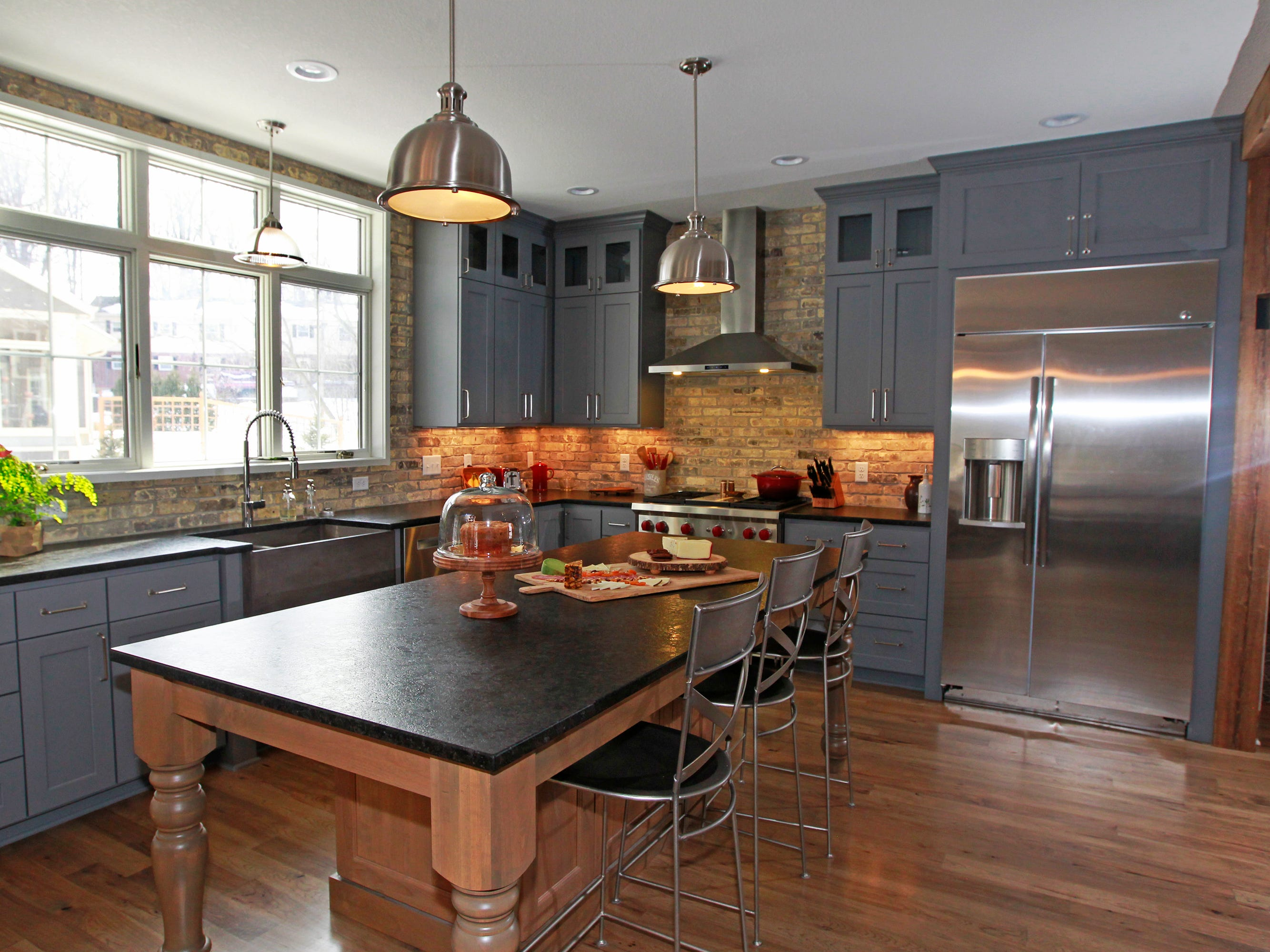 The Goransons' kitchen has reclaimed Cream City bricks, a leathered granite island, large picture window and recess and pendant lighting fixtures.