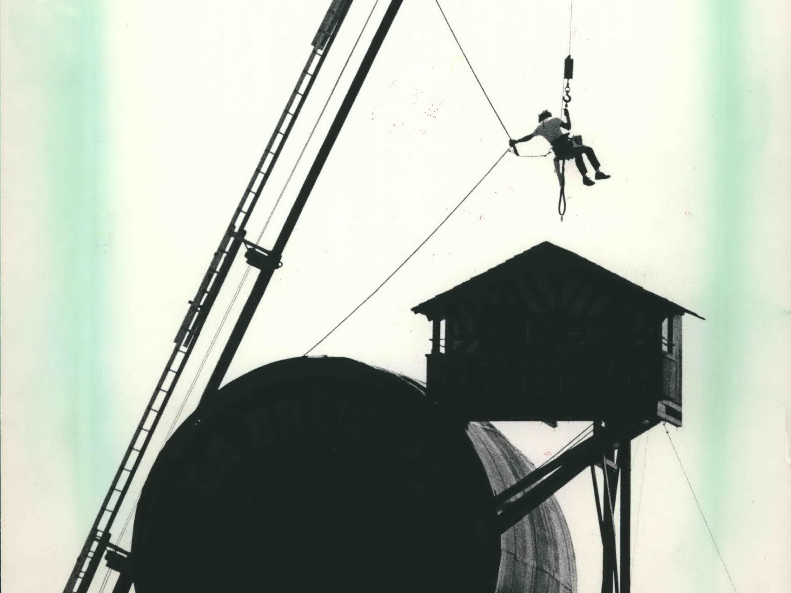 A worker is raised to the roof of the County Stadium chalet on July 12, 1983. A crew from Derse Sign Co. was doing routine maintenance on Bernie Brewer's chalet - which, it turned out, would be taken down after the 1984 season. This photo was published in the July 13, 1983, Milwaukee Sentinel.