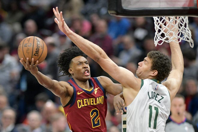 Cavaliers guard Collin Sexton shoots the ball around Bucks center Brook Lopez in the first quarter Wednesday at Quicken Loans Arena.