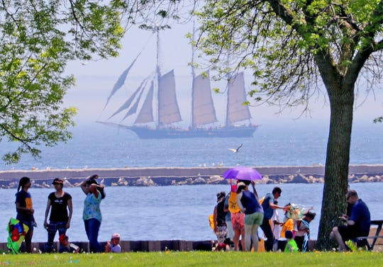 The Denis Sullivan sails on Lake Michigan as people enjoy the lakefront at the 31st annual family kite festival, sponsored by Gift of Wings and the Kite Society of Wisconsin and Illinois.