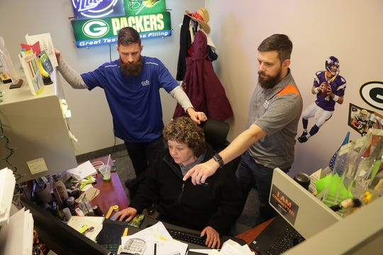 CCB Technology employees Kyle Jolly (right), director of sales, and Steve Scherer, vice president of sales, gather around Paula Rorek, national account manager, on March 7 as they go over orders at CCB Technology in Racine.