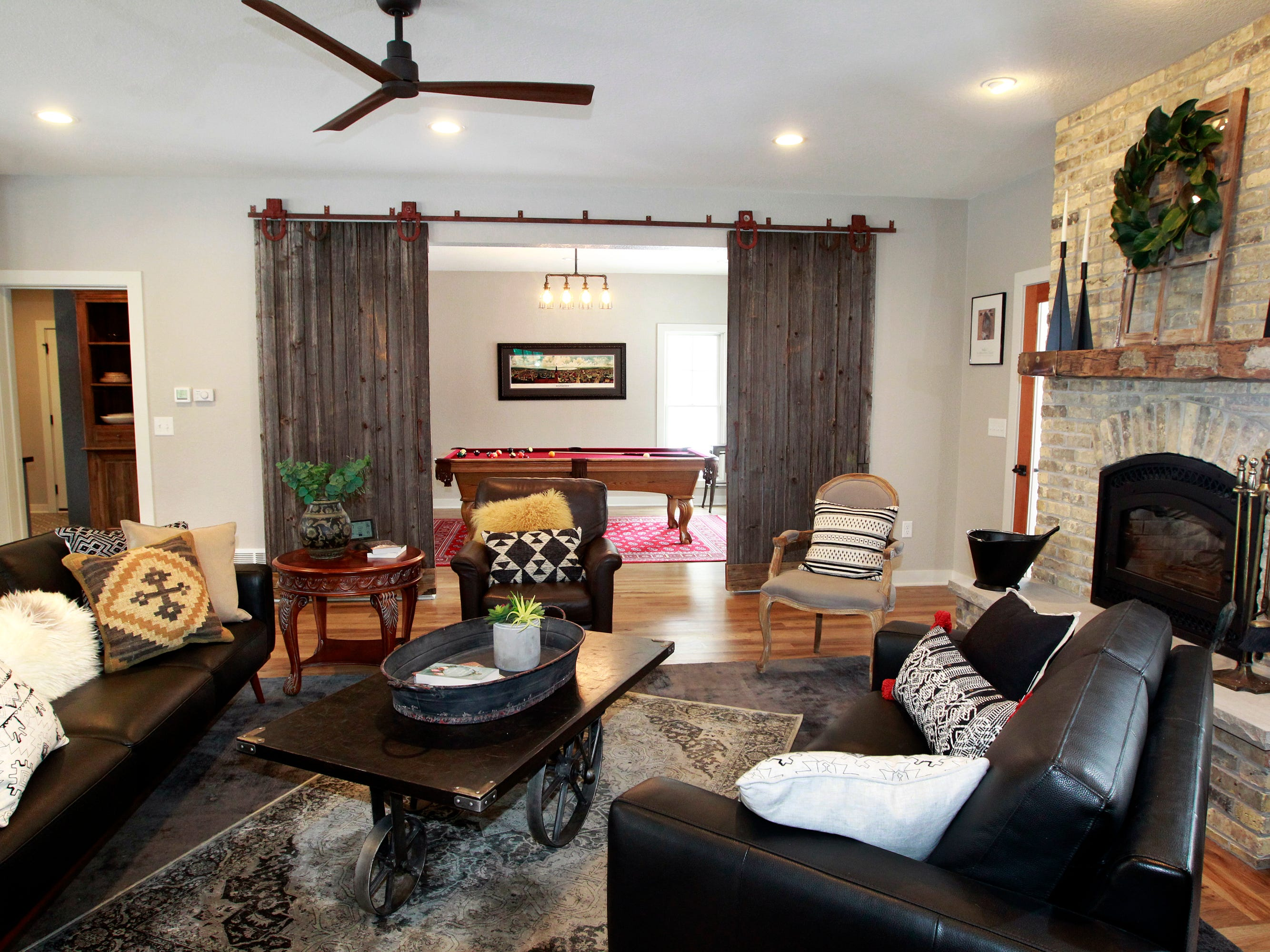 A reclaimed barn door leads from the living room to the game room.