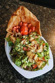 Fattoush salad, shown with a fried pita bowl, contains bits of fried bread and is tossed with a savory-sweet dressing at Pita Palace.