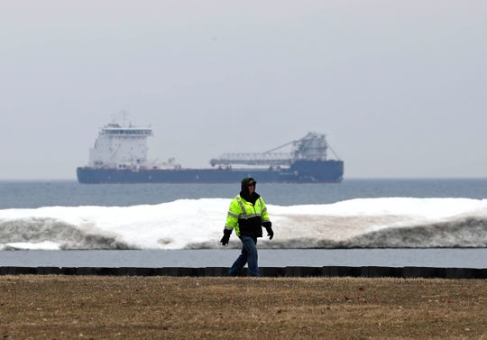 A pedestrian walks on the lakefront in early Spring. Heavy winter snow and ice finally melts into Lake Michigan along the Milwaukee Harbor along the lakefront.  Several climate change researchers are warning about possible changes to Lake Michigan and the other Great Lakes through climate change.