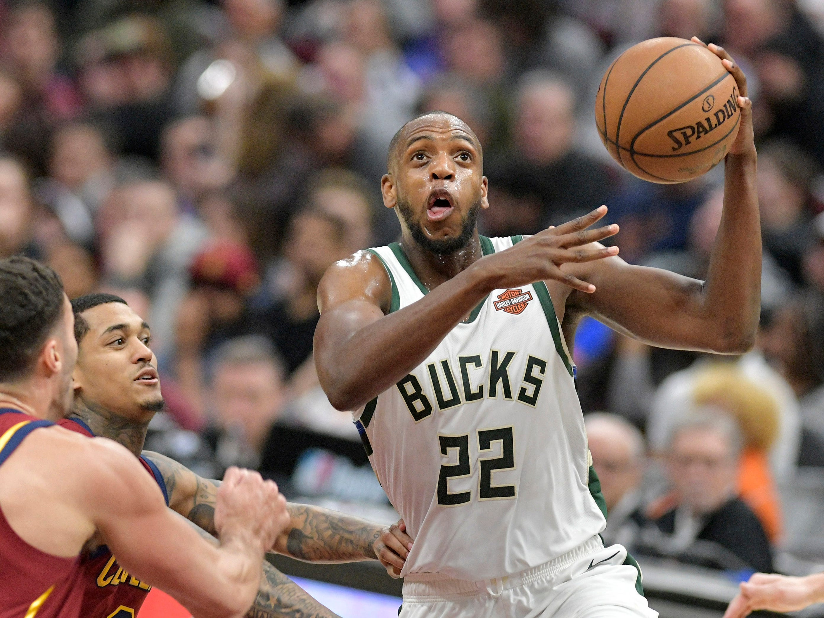 Bucks forward Khris Middleton (22) gets ready to go up for a shot against Larry Nance Jr. (left) and Jordan Clarkson of the Cavs in the third quarter.