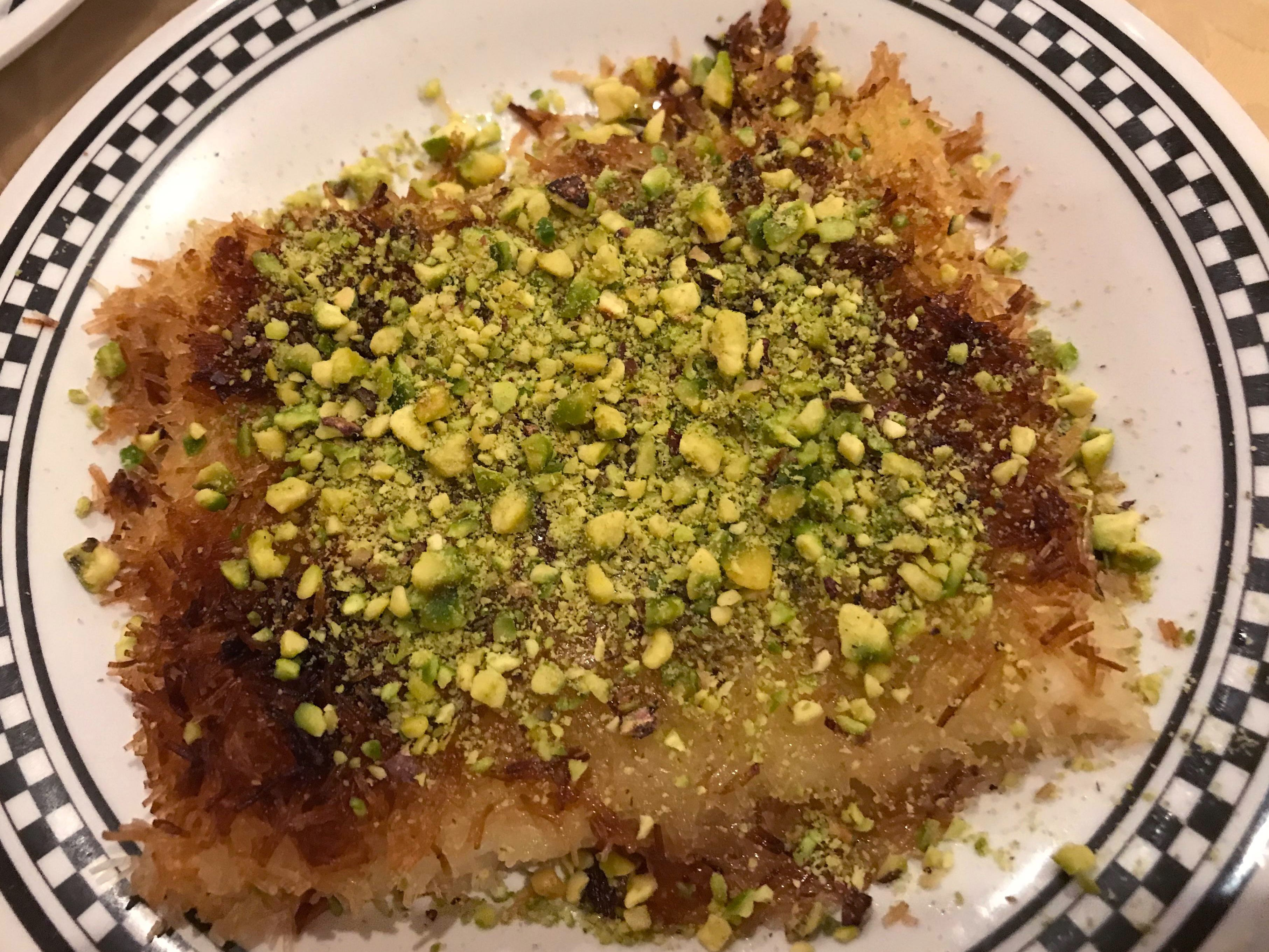 Kunafa, a dessert of cheese layered between shredded phyllo dough, covered in chopped pistachios and sweetened with sugar syrup, is one of the desserts at Damascus Gate.
