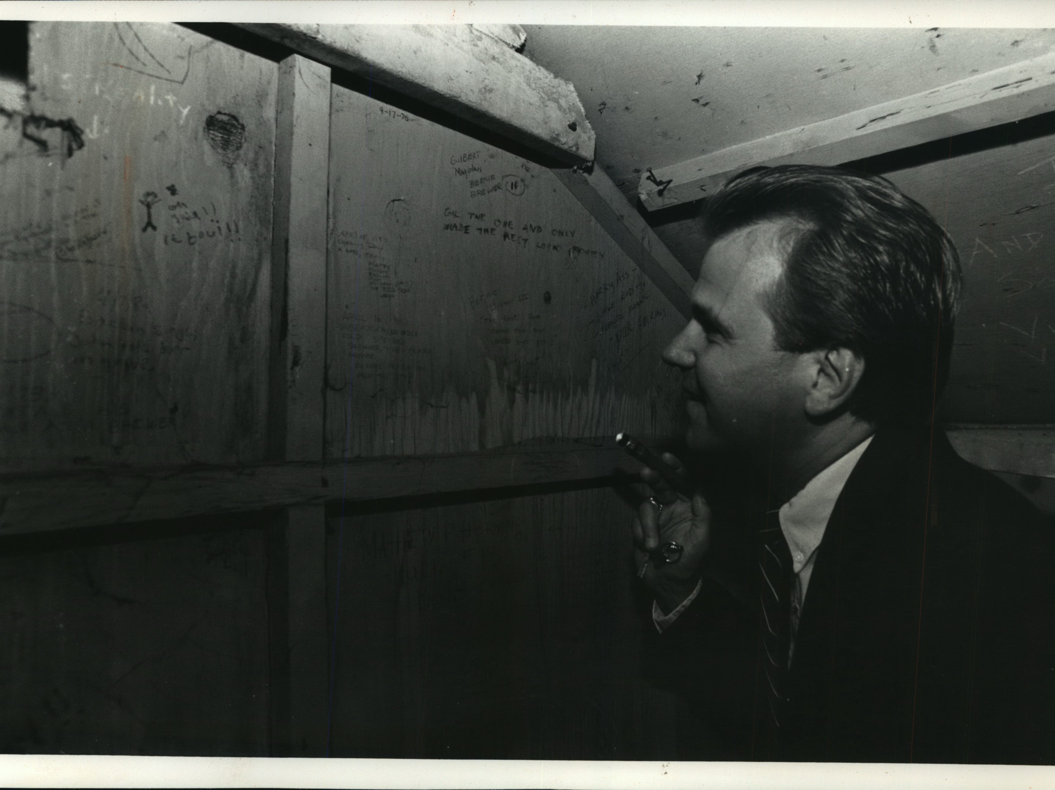Mark Paget, a member of the County Stadium grounds crew who was Bernie Brewer from 1974 to '76, reads graffiti he wrote on the walls of the old chalet, where he cheered on the home team above a giant beer keg and mug. This photo was published in the July 8, 1992, Milwaukee Journal.