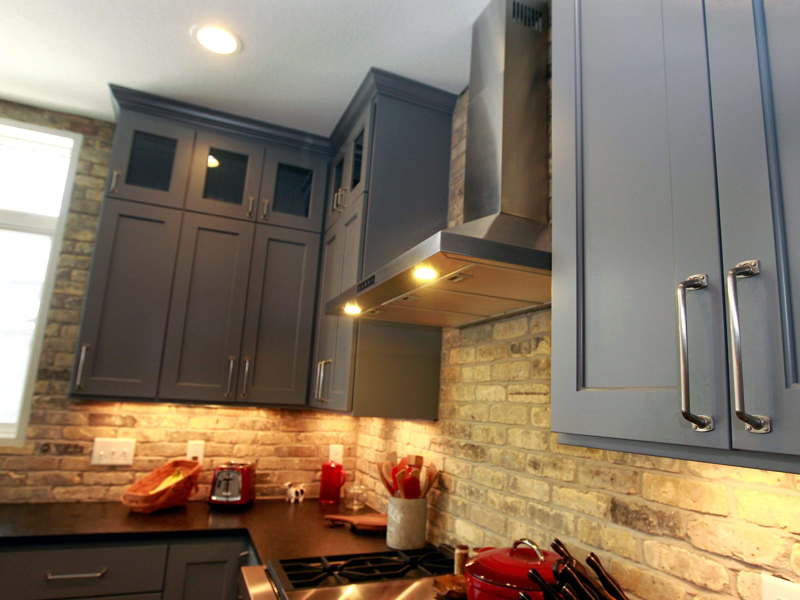 The kitchen's custom cabinets are a gray shade with a bit of blue, and they go to the ceiling.