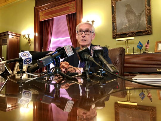 Gov. Tony Evers meets with reporters in his office at the Wisconsin State Capitol Thursday. Evers said he won't move quickly to exercise powers that were eliminated under laws a Dane County judge blocked Thursday.