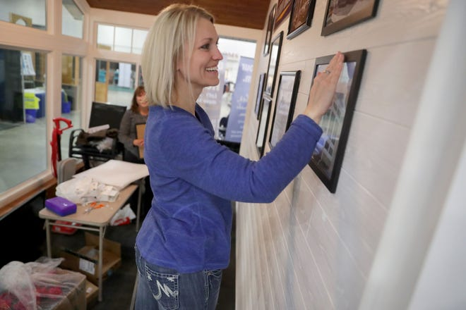 Colleen Gallo, an office manager with S.E. Wisconsin Sunrooms in Wind Lake, hangs photos at the 95th Annual Realtors Home & Garden Show in 2018. This year's event is March 20-29.
